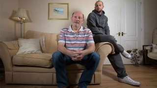 photo of John Edgington sitting on a settee with son Matthew Edgington sitting behind him on the settee arm